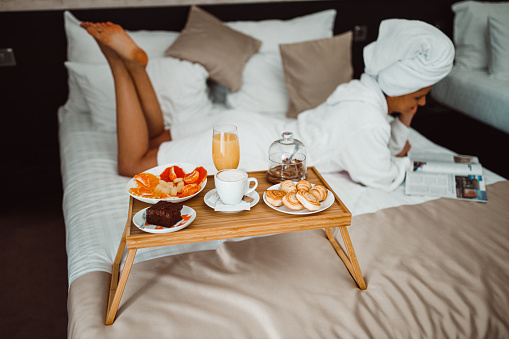 683349444 istock photo Woman eating breakfast in bed and reading a magazine 1265191087