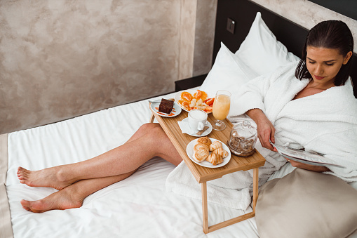 683349444 istock photo Woman eating breakfast in bed and reading a magazine 1265191103