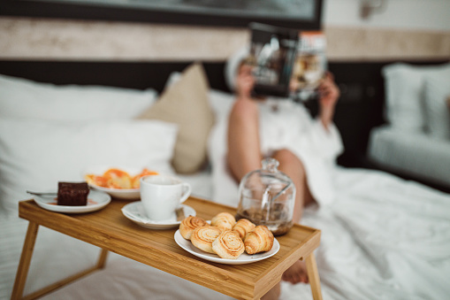 683349444 istock photo Woman eating breakfast in bed and reading a magazine 1265191116