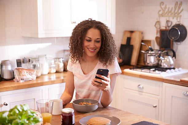 Woman Eating Breakfast Whilst Using Mobile Phone Woman Eating Breakfast Whilst Using Mobile Phone one mid adult woman only stock pictures, royalty-free photos & images