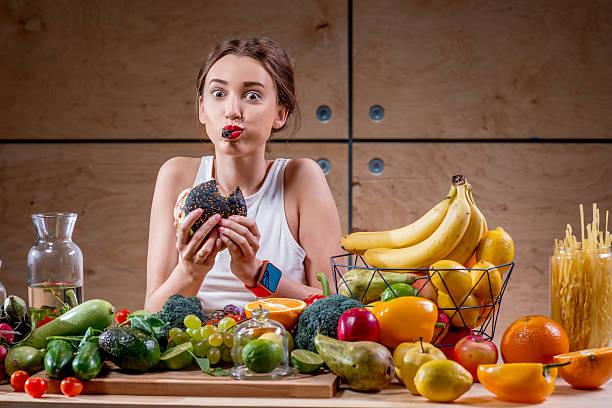 kobieta jedzenie burger w tabeli pełna zdrowej żywności - duża grupa obiektów zdjęcia i obrazy z banku zdjęć