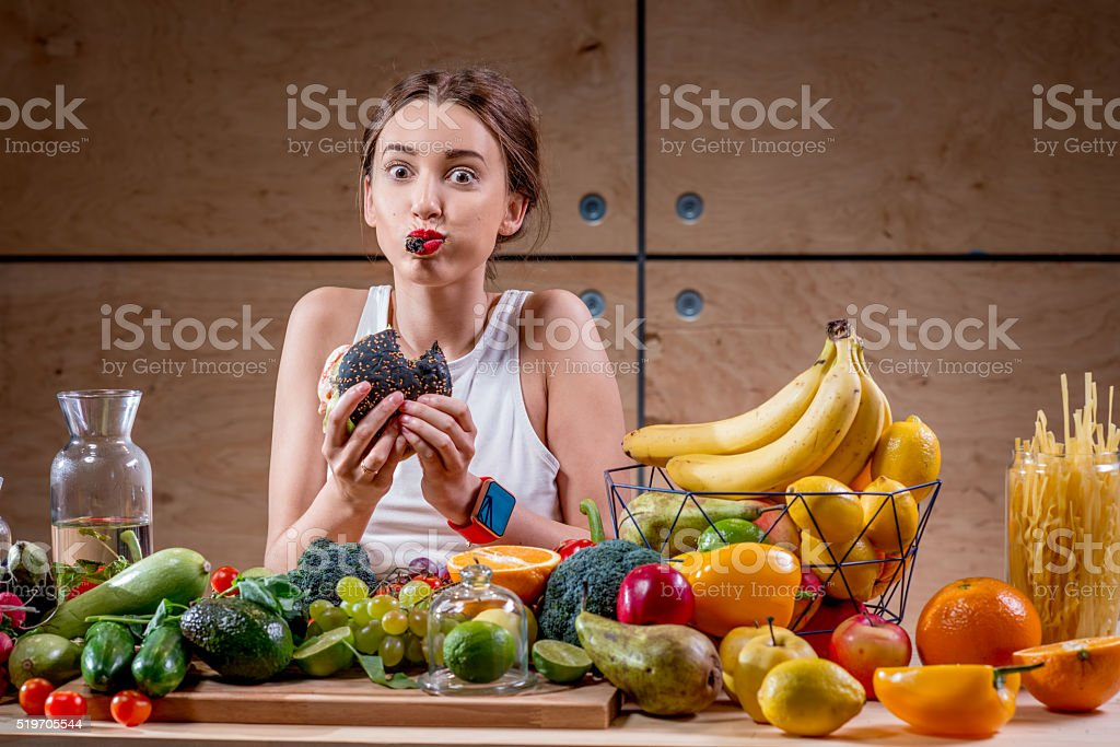Woman eating burger at the table full of healthy food stock photo