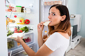 Woman Eating Cheese In Front Of Refrigerator