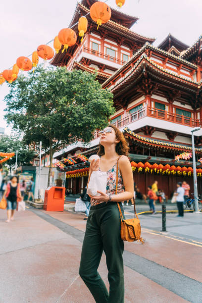 woman eating chinese bun    in chinatown in singapore - vacations food stock pictures, royalty-free photos & images