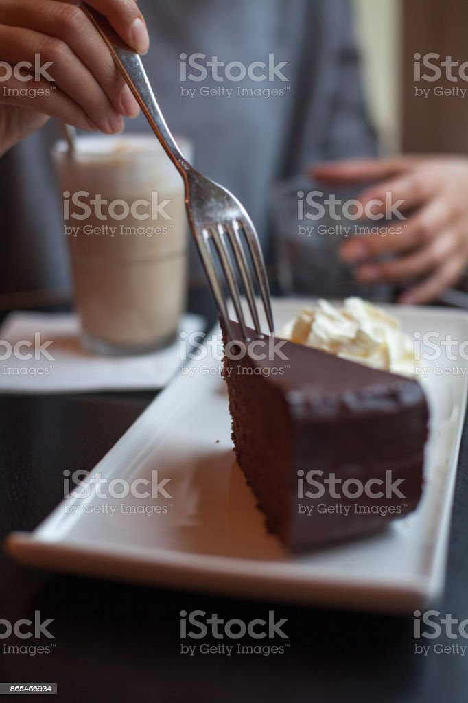 Woman eating Chocolate cake at the cafe stock photo
