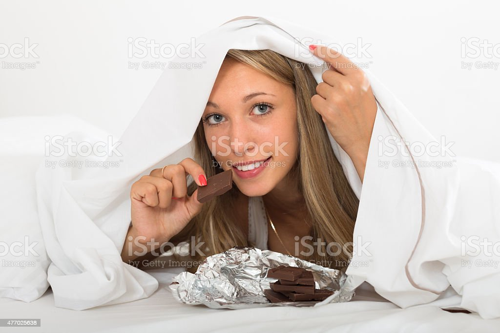 Woman eating chocolate in bed stock photo