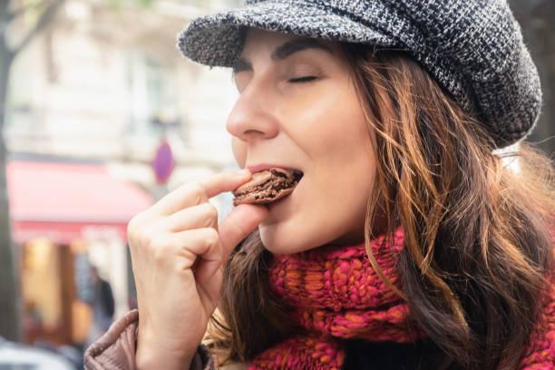 Woman eating chocolate macaron on street in Paris stock photo