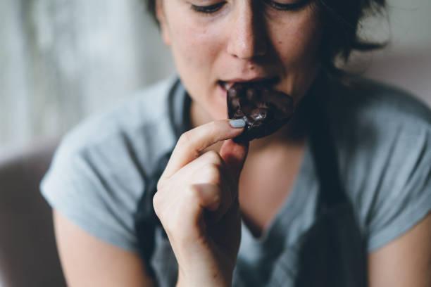 vrouw eten van chocolade - pure chocola stockfoto's en -beelden
