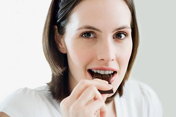 woman eating chocolate - pure chocola stockfoto's en -beelden