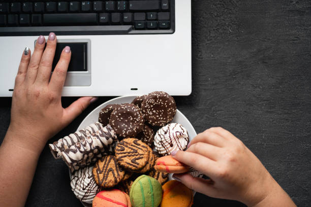 Woman eating cookies and coffee at workplace Unhealthy snack at work time. Compulsive indulgence, overeating, stress, high calorie, fattening junk food, weight gain. Woman eating cookies at workplace large group of objects stock pictures, royalty-free photos & images