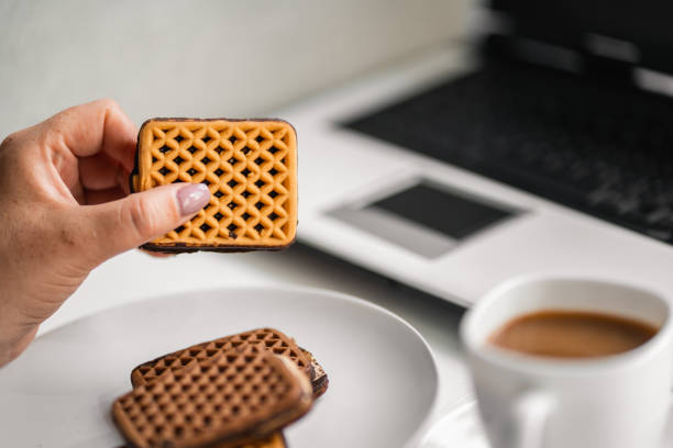 Woman eating cookies and coffee at workplace stock photo