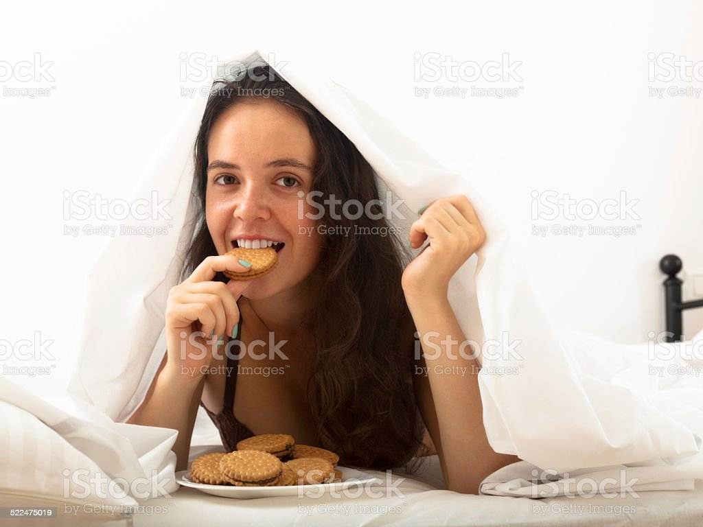 Woman eating cookies in bed stock photo