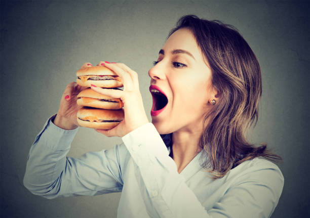 woman eating craving a tasty double burger - serving size stock photos and pictures