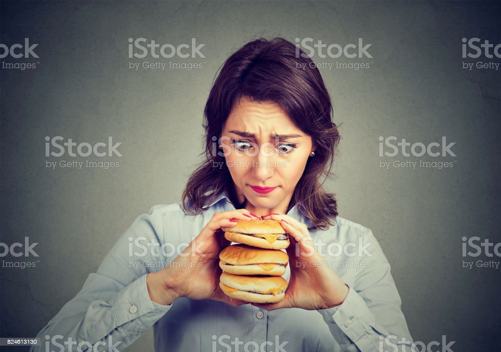 Woman eating craving a tasty triple burger stock photo