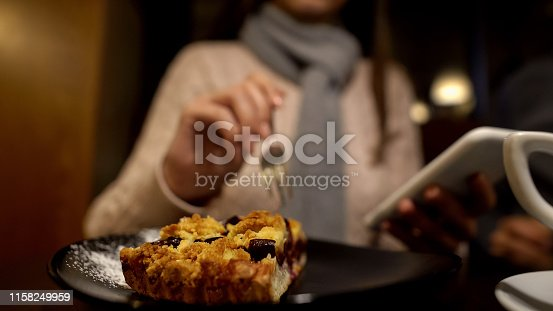 istock Woman eating delicious pie and using phone, enjoying free time alone, close up 1158249959