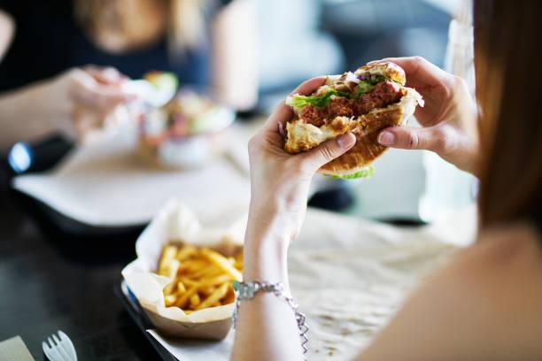 vrouw eten eten veganistische vleesloze hamburger in restaurant foto