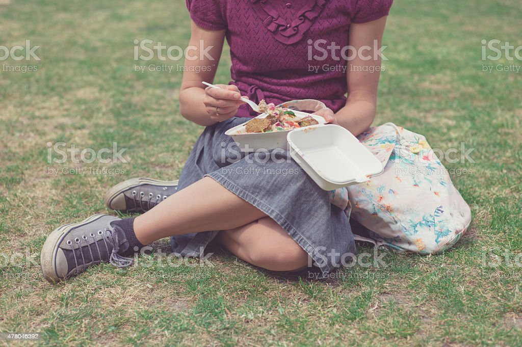 Woman eating falafel in park stock photo