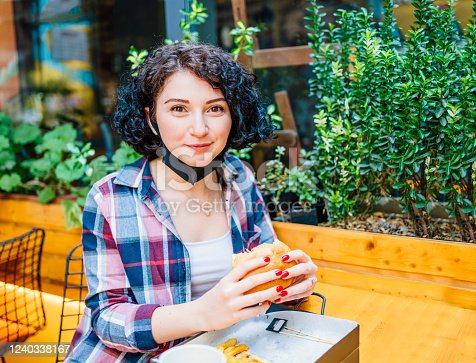 istock Woman Eating Fastfood Burger In Face Mask 1240338167