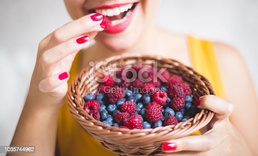The young woman smiles while holding and eating from a basket filled with raspberries and blueberries