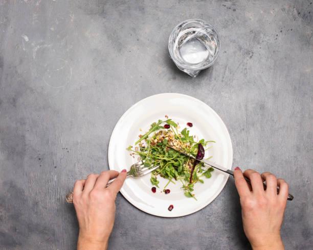 Frau essen frische grüne Sprossen Microgreens und Samen in weißer Platte auf grauem Hintergrund mit Silberbesteck und Kopierraum.  Hände. Diätetische Ernährung. Kleine Portion, Gewichtsverlust Konzept. – Foto