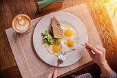 Top view of female hands holding fork and knife while having tasty breakfast at modern european cafe. Young woman eating fried eggs with toasts and morning coffee at restaurant