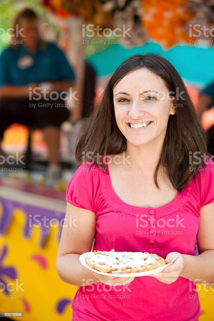 Woman Eating Funnel Cake at a Carnival stock photo