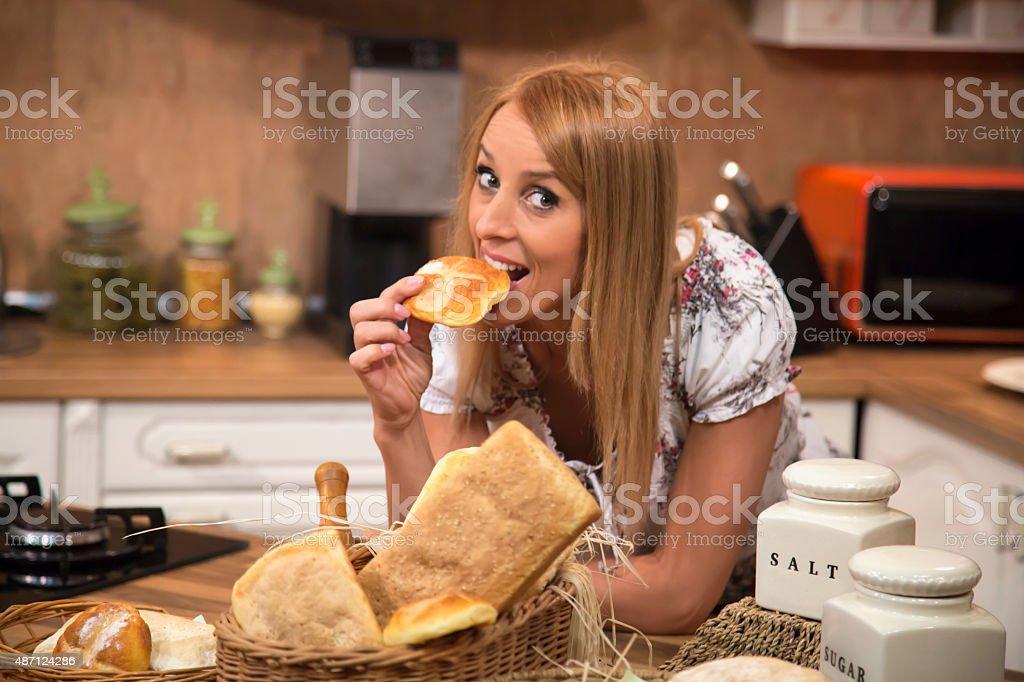 Woman eating gluten free bun in kitchen. stock photo