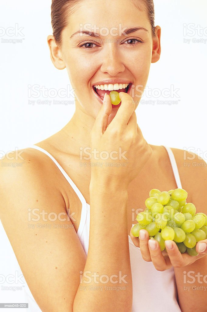 Woman eating grapes royalty free stockfoto