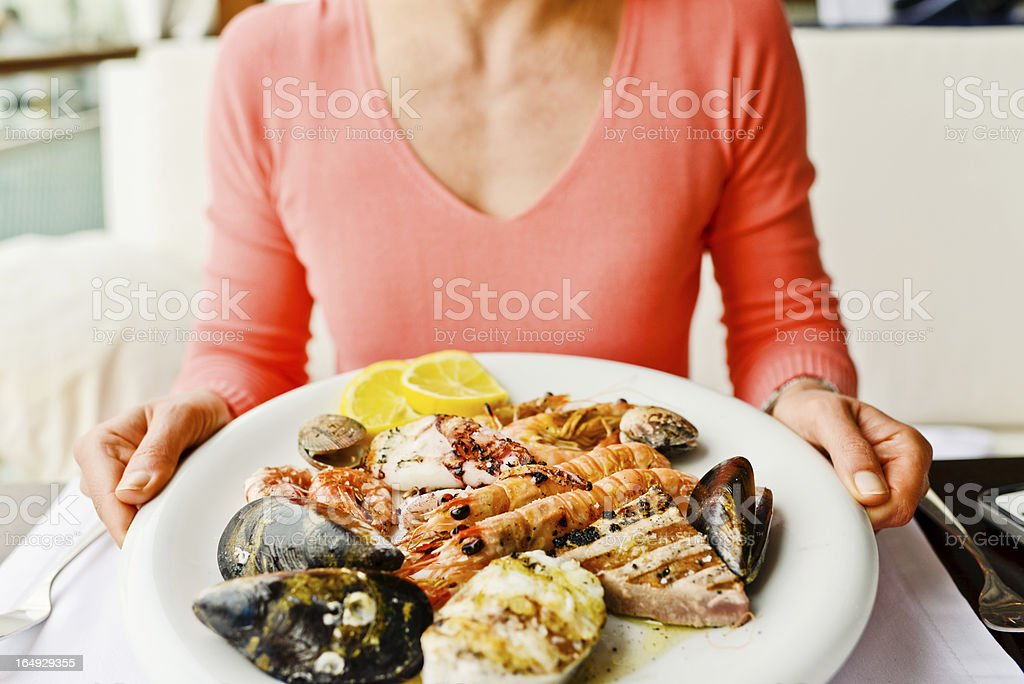 Woman eating Grilled Seafood in a restaurant stock photo