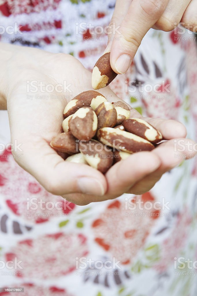 Woman Eating Handful Of Brazil Nuts stock photo