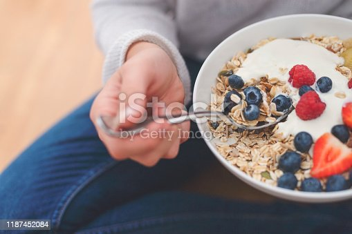 Woman Eating healthy breakfast bowl. It includes strawberries, blueberries, kiwifruit, granola, muesli  and yoghurt. Clean eating, dieting, detox, vegetarian food concept. Shot from above
