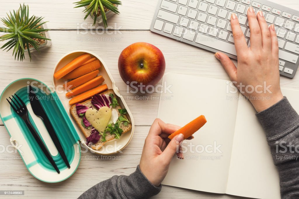 Woman eating healthy dinner from lunch box at her working table stock photo