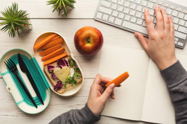 vrouw eten gezond diner uit de doos van de lunch op haar werktafel - snack stockfoto's en -beelden