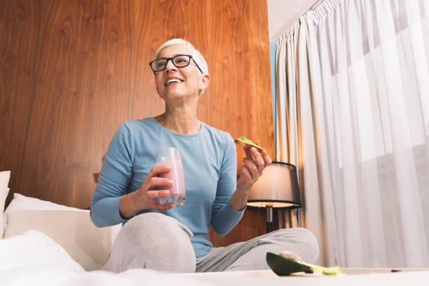 Mulher que come o jantar saudável em sua cama - foto de acervo