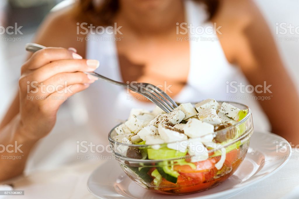 Woman Eating Healthy fresh Salad with Cheese stock photo