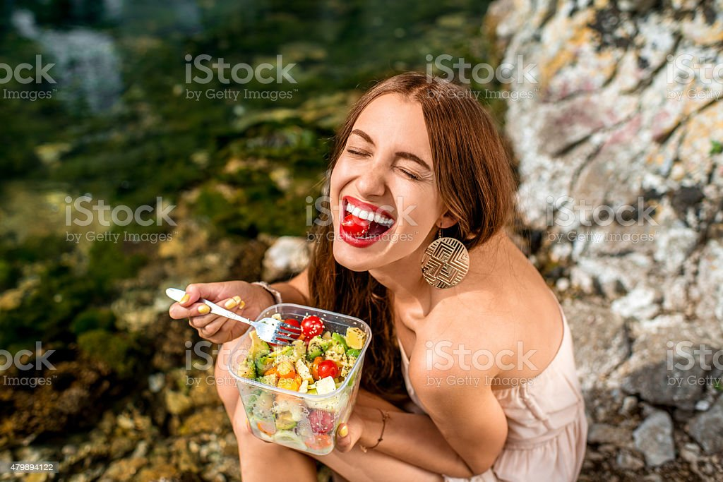 Woman eating healthy salad near the river royalty-free stock photo
