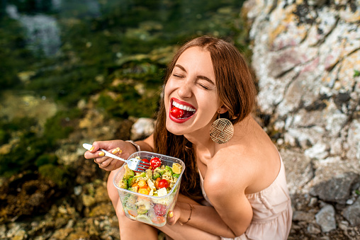 Woman Eating Healthy Salad Near The River Stock Photo - Download Image Now