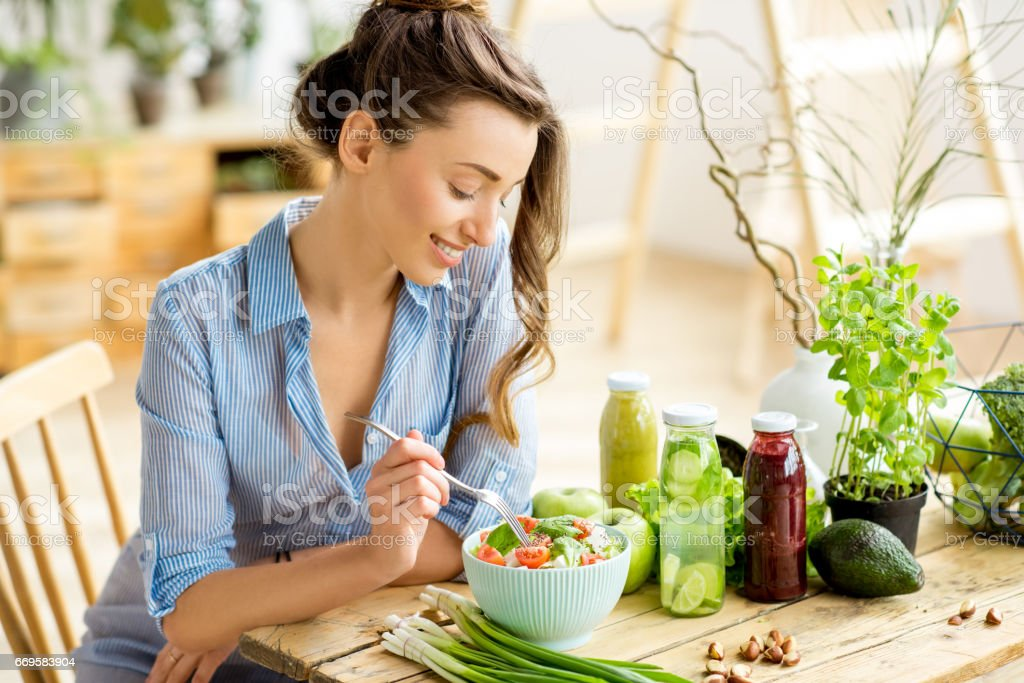 Woman eating healthy salad Young and happy woman eating healthy salad sitting on the table with green fresh ingredients indoors Adult Stock Photo
