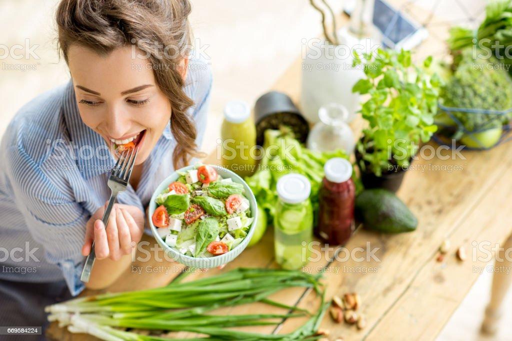 Woman eating healthy salad stock photo