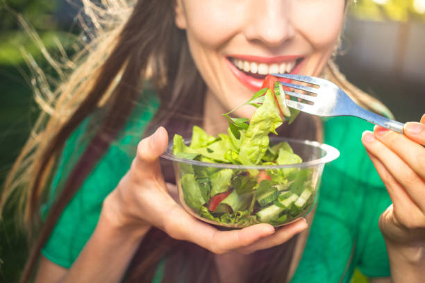 Woman eating healthy salad stock photo