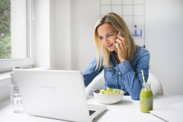 Woman eating healthy vegetable salad while talking on mobile phone at workplace stock photo