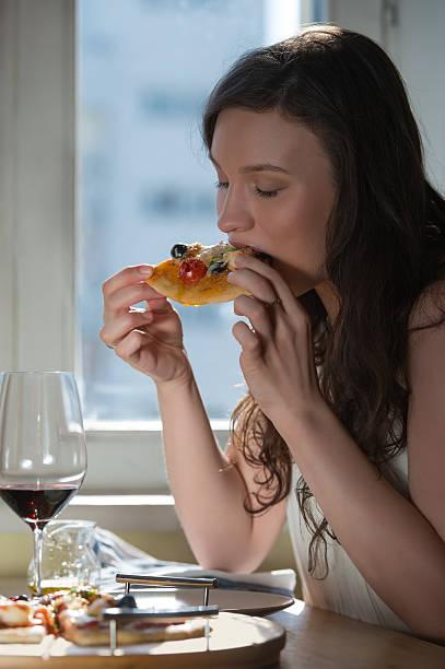 woman eating homemade pizza and drinking red wine - oliven wohnzimmer stock-fotos und bilder
