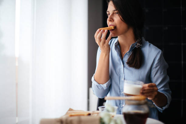 Woman eating honey on toasted bread Woman eating honey on toasted bread female sandwich stock pictures, royalty-free photos & images