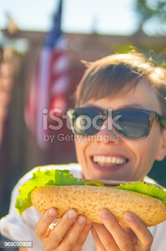 534317162 istock photo Woman eating hot dog over american flag 969090908