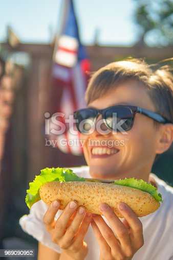 534317162 istock photo Woman eating hot dog over american flag 969090952