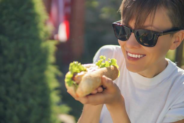 mulher comendo cachorro-quente - junk food - fotografias e filmes do acervo