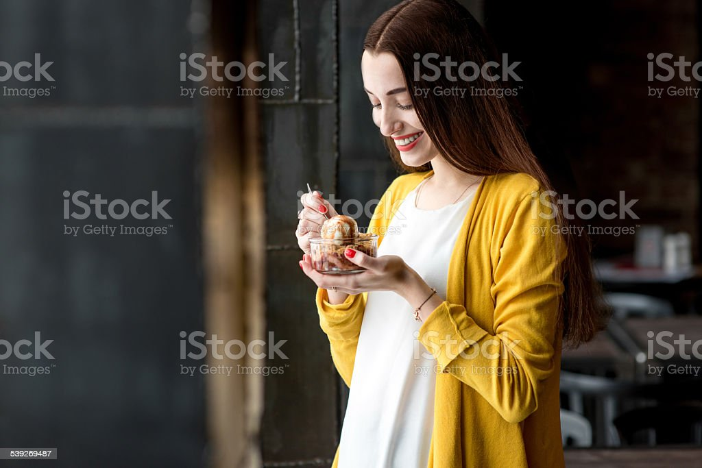 Woman eating ice cream in the cafe stock photo