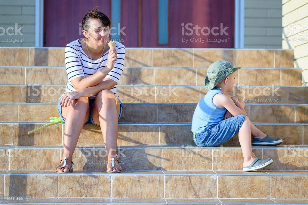 Mulher comendo sorvete perto Sulking menino - foto de acervo