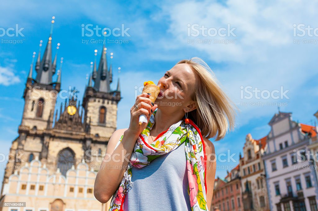 woman eating ice cream on a background of Tyn Cathedral stock photo