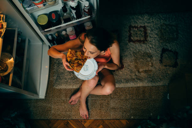 Woman eating in front of the refrigerator in the kitchen late night stock photo